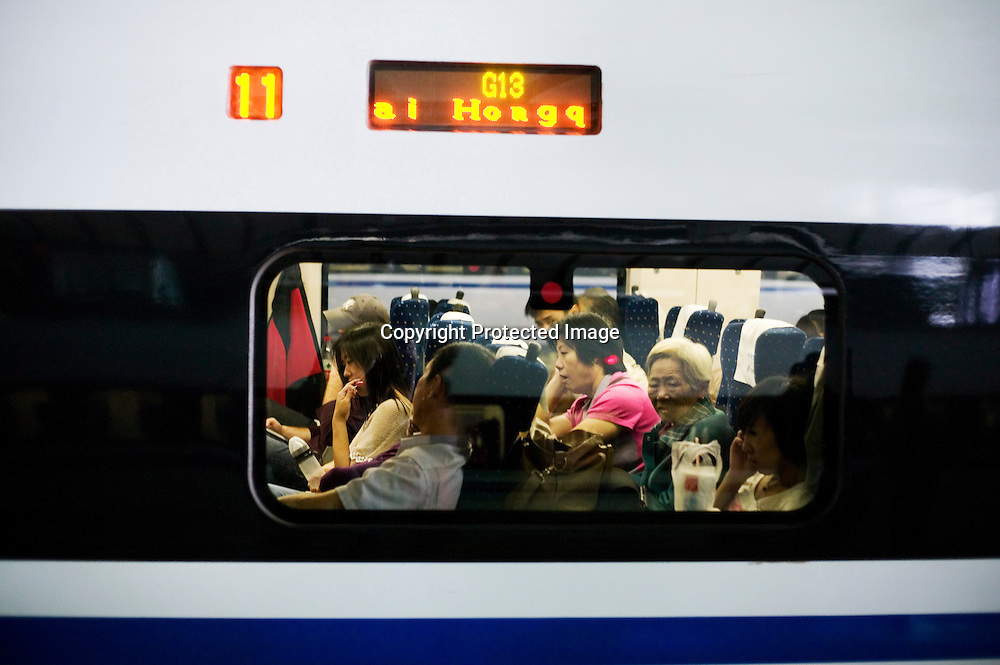 Beijing, September 11 , 2011 : passengers look out of the window. The passenger-dedicated trunk line opened in June 2011, reducing the 1,318 km journey between Beijing and Shanghai to less than 5 hours. Trains reach top speeds of 300 km/h (186 mph) for the entire trip.