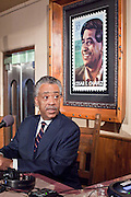 "19 JUNE 2009 -- PHOENIX, AZ: With a portrait of Latino civil rights leader Ceasar Chavez behind him, Rev Al Sharpton on the radio at El Portal Friday. Rev. Al Sharpton is in Phoenix Friday to protest the high profile ""crime suppression"" sweeps conducted by the Sheriff's Department. Critics contend the sweeps use racial profiling to target Hispanics.  PHOTO BY JACK KURTZ"