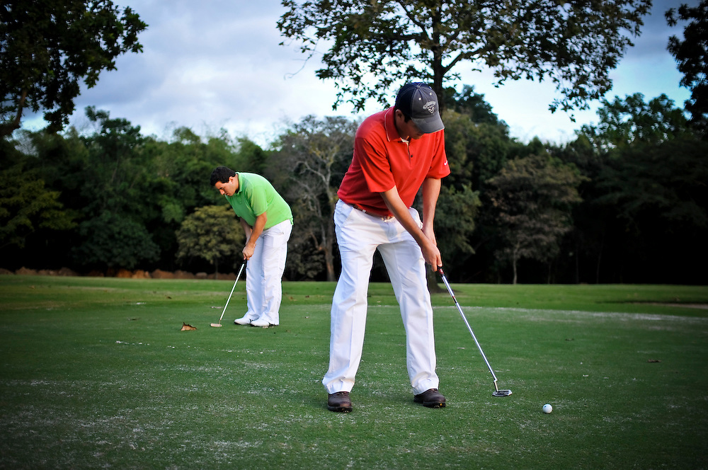 """(Left) Ernesto Martinez, 30, the 2009 Caracas Country Club golf champion, practices putting. Venezuelan President, Hugo Chávez recently signaled plans to expropriate the club in order to use the property to build thousands of low cost apartments for the city's poor.  """" We feel that our property has been stolen,"""" Martinez said."""