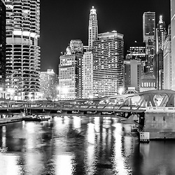 Chicago River Clark Street Bridge at night panorama photo in black and white. Picture includes the London Guarantee building, Hotel 71, Marina City Tower, and other downtown Chicago buildings looking East down the Chicago River. Panorama photo ratio is 1:3.