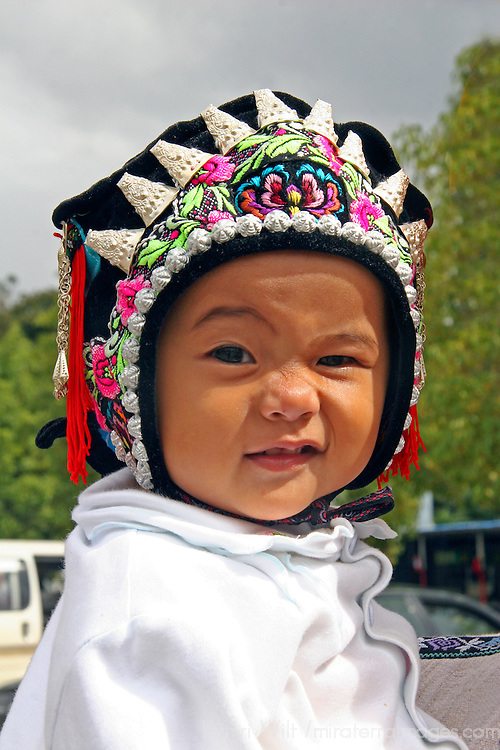 Asia, China, Kunming. Ethnic minority baby in traditional headwear.