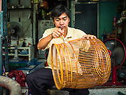 03 AUGUST 2016 - BANGKOK, THAILAND: An artisan who makes fancy bird cages varnishes some of his cages in front of his home in the Pom Mahakan Fort slum. Residents of the slum have been told they must leave the fort and that their community will be torn down. The community is known for fireworks, fighting cocks and bird cages. Mahakan Fort was built in 1783 during the reign of Siamese King Rama I. It was one of 14 fortresses designed to protect Bangkok from foreign invaders. Only of two are remaining, the others have been torn down. A community developed in the fort when people started building houses and moving into it during the reign of King Rama V (1868-1910). The land was expropriated by Bangkok city government in 1992, but the people living in the fort refused to move. In 2004 courts ruled against the residents and said the city could take the land. Eviction notices have been posted in the community and people given until April 30 to leave, but most residents have refused to move. Residents think Bangkok city officials will start evictions around August 15, but there has not been any official word from the city.      PHOTO BY JACK KURTZ