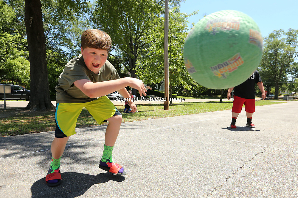 Evan Sheffield, 13, a student at Milam, hits the ball into the next square as he tries to get a classmate out while playing Four Square during Field Day on Monday.
