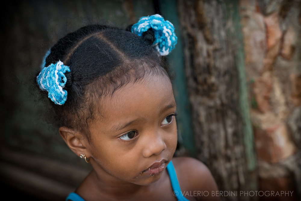 A little girl, her mouth with some bread crumbles left from a snack, looks at what is going on in front of her house in Trinidad, Cuba.