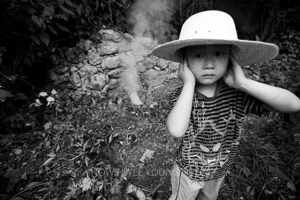 A boy from Cangfang village covers his ears from the noise of firecrackers during a last visit to his family's ancestral tomb before relocation to neighbouring Hui county to make way for the colossal South-to-North Water Transfer project in Xichuan county of Henan Province in China on 28 June 2010. The central route, which will raise the height of the Danjiangkou reservoir dam from 162 meters to 176.6 meters, requires the relocation of 330,000 people in Henan and Hubei provinces. Xichuan, a remote, mountainous region inaccessible by railway, is home to 162,000 would-be SNWD migrants, the most anywhere. The South-to-North Water Transfer project, the largest known water diversion project, was conceived in 1952 to solve the country's chronic water shortages and involves creating three routes to channel 44.8 billion cu m of water from southern China to the northern areas. As part of the project's central route, affecting Henan and Hubei provinces, water from the Danjiangkou reservoir will be diverted to Beijing. Parts of Xichuan county, a remote, mountainous region inaccessible by railway and home to 162,000 migrants, the most anywhere, will be completely submerged by water from the Danjiangkou reservoir by 2014. The vast resettlement of affected residents in Xichuan county began in August 2009 and lasted till 2011.