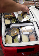 A volunteer packs meals in a case for Meals On Wheels at Horizons, 819 5th Street SE in Cedar Rapids on Wednesday morning, June 1, 2011.
