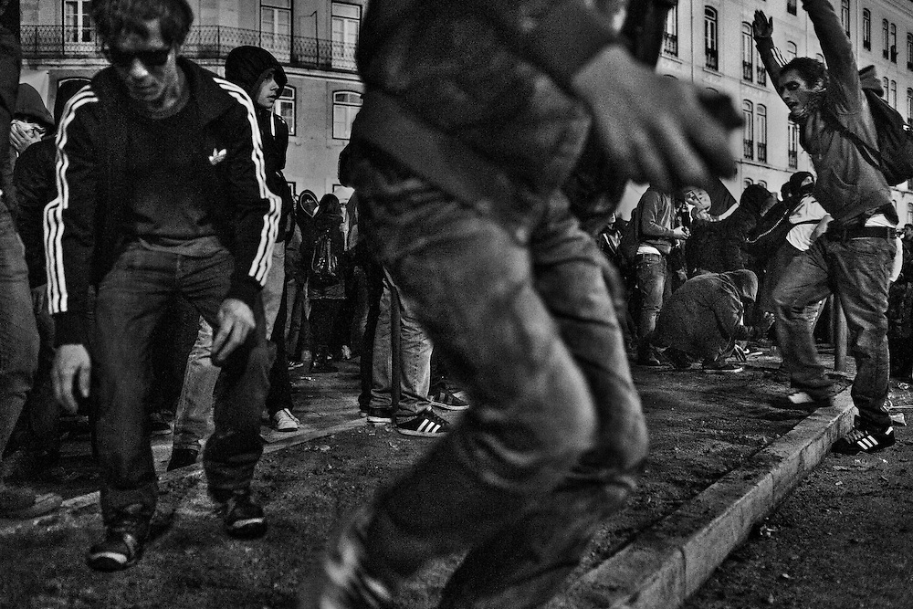 Protestors disassemble the sidewalk to throw rocks towards the cordon of riot police officers by the stairway of the Congress during a demonstration to marking the European coordinated general strike in Lisbon, Portugal, on November 14, 2012. Around 1.4 million people are currently unemployed in Portugal, and only 370,000 of them have receiving monthly social support from the government, leaving around 1 million people without the benefit. Over youths, unemployment rates is breaking records reaching 39% in the third quarter of the year, or equivalent to more than 175,000 people. The official unemployment rate in Portugal is currently on 15.7%, a bit away from the highest European rate in Spain, with 25.8%, followed by Greece with 25.1% of jobless. Photo by Mauricio Lima for The New York Times