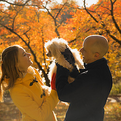 A couple holding up their dog between them, surrounded by trees in autumn.