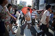 TOKYO, JAPAN, Shibuya August 05 - A woman hides herself from the sun with a red umbrella ! Tokyo is very hot ; over 33° C degres. August 2012 [FR] une femme se protege des rayons du soleil avec une ombrelle rouge. Tokyo est très chaud en ete, plus de 33° C
