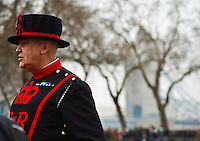 A beefeater stands in front of Tower Bridge at the Tower of London, London, England.
