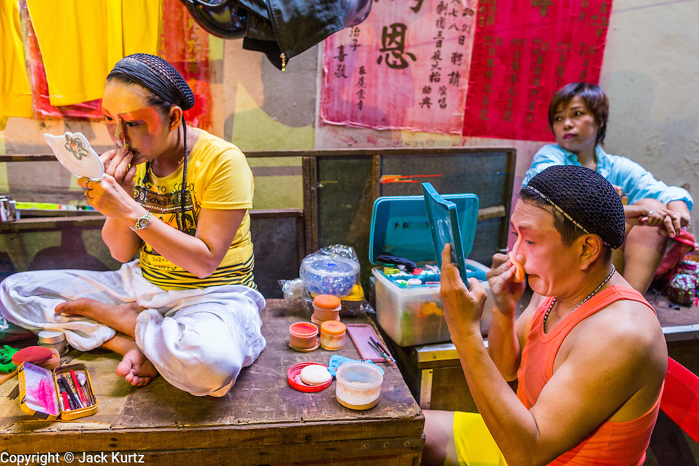 27 APRIL 2013 - BANGKOK, THAILAND: Chinese opera performers put on their makeup in an alley in Talat Noi, a neighborhood in Bangkok's Chinatown. Chinese opera is popular in Thailand and is usually performed in the Teochew language. Millions of Chinese emigrated to Thailand (then Siam) in the 18th and 19th centuries and brought their cultural practices with them. There are as many 30 Chinese opera troupes left in Bangkok. They travel from Chinese temple to Chinese temple performing on stages they put up in streets near the temple, sometimes sleeping on hammocks they sling under their stage. The opera troupes are paid by the temple, usually $700 to $1000 a night.    PHOTO BY JACK KURTZ