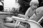 "A young girl of nearly four plays on garden furniture with her younger brother in the back garden of their South London house. The boy is blonde-haired with a healthy tummy storing energy for his games and boyhood fantasies while his sister lies on the soft cushion of the chair during this warm summer afternoon. From a personal documentary project entitled ""Next of Kin"" about the photographer's two children's early years spent in parallel universes. Model released."