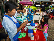 27 AUGUST 2016 - BANGKOK, THAILAND: A woman makes traditional Thai crushed ice desserts during a lunch for residents of the Pom Mahakan slum. The Pom Mahakan community is known for fireworks, fighting cocks and bird cages. Mahakan Fort was built in 1783 during the reign of Siamese King Rama I. It was one of 14 fortresses designed to protect Bangkok from foreign invaders. Only two of the forts are still standing, the others have been torn down. A community developed in the fort when people started building houses and moving into it during the reign of King Rama V (1868-1910). The land was expropriated by Bangkok city government in 1992, but the people living in the fort refused to move. In 2004 courts ruled against the residents and said the city could evict them. The city vowed to start the evictions on Sept 3, 2016, but this week Thai Prime Minister Gen. Prayuth Chan-O-Cha, sided with the residents of the fort and said they should be allowed to stay. Residents are hopeful that the city will accede to the wishes of the Prime Minister and let them stay.       PHOTO BY JACK KURTZ