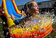 Grace Harrison, 5, takes a plunge down the water slide during the Family Fun Day at First General Baptist Church in Jackson, Mo., on Saturday, July 24, 2010. The event included archery, a water slide, face painting, horseback riding, and other activities for kids.