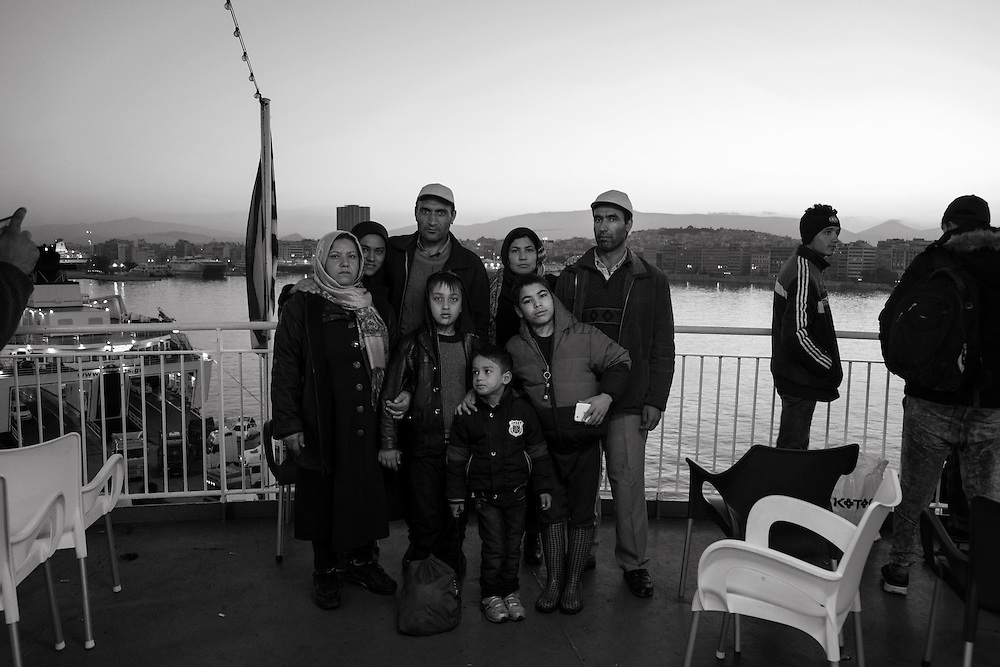 A group of migrants pose for a picture while they wait to disembark from a ferry that brought them to Piraeus port  from Lesbos on November 18, 2015. Since the start of the summer, the Greek island of Lesbos has assumed notoriety as the main gateway into Europe for thousands of desperate refugees that continue to cross the Aegean sea from Turkey daily.