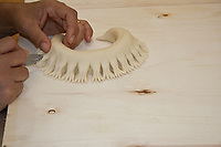 hands carving a bread shape using a knife on wooden counter, Sardinian bread sculpture, the Pani Pintau