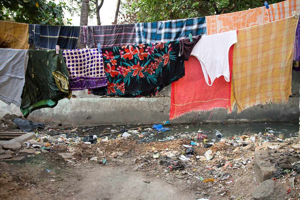 Raw sewage and trash floods the backyard of a woman living in a slum in Chennai, India. She says during the flooding season, the water will be consistently at thigh height, mixed with trash and sewage.