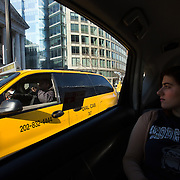 WASHINGTON, DC - APR 4:  Shira Lebow, passes a taxi as she takes an UberX with driver Sanjiv Kumar, to her job at the Living Social office, April 9, 2014, in Washington, DC. <br /> <br /> Kumar, a former Washington Flyer driver, now drives solely for UberX. Thousands of local car owners have signed up in recent months to drive with one of the &quot;ride-share&quot; operators that use smartphone apps to link people needing rides with car owners willing to give them, for a price. (Photo by Evelyn Hockstein/For The Washington Post)