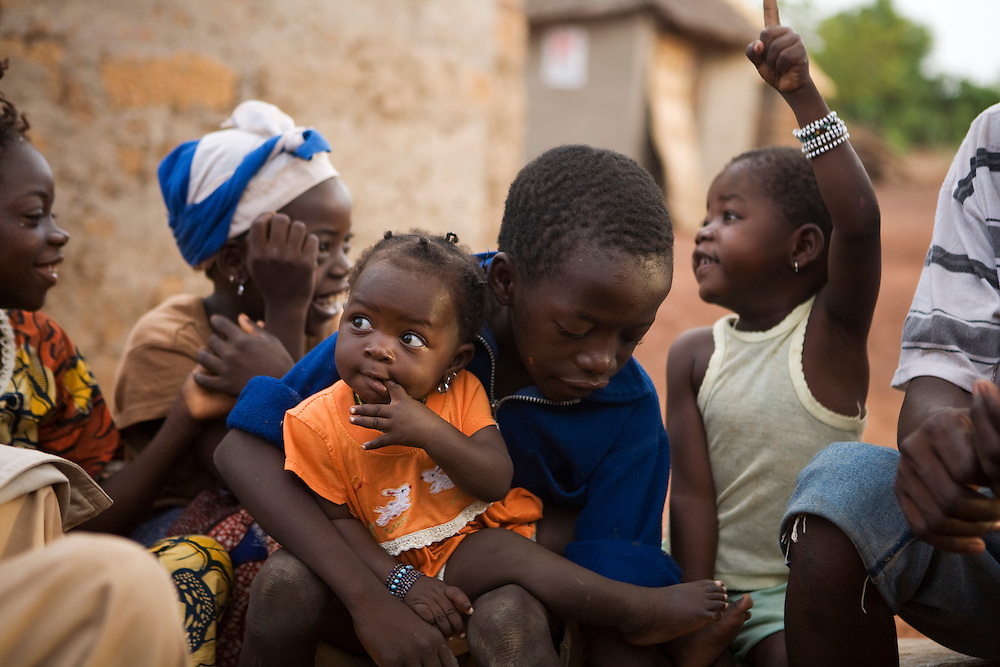 The village chief Valy Diakite's children chatting outsides their home early in the morning  before going to school. Sogola, Mali.