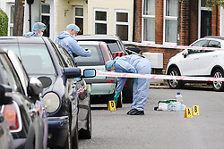 © Licensed to London News Pictures. 19/06/2019. London, UK. A forensic officer places an evidence marker on Wellbeck Road, Barnet, North London where three men were found to be suffering stab injuries on Tuesday 18 June 2019, just before 11pm. A man in his 30s was treated at the scene, but he was pronounced dead shortly after midnight. Two other men – one in his 20s and one in his 30s were taken to hospital for treatment.  Photo credit: Dinendra Haria/LNP