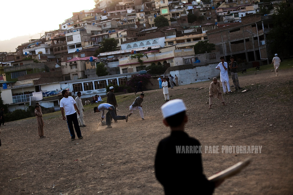 ABBOTTABAD, PAKISTAN - MAY 9: Pakistani boys play cricket on the outskirts of Abbottabad, on May 9, 2011 in Abbottabad, Pakistan. The town of Abbottabad became infamous after the US launched a midnight raid on a compound housing Osama bin Laden in the garrison town, on May 2, 2011. The operation, code-named Operation Neptune Spear, was launched from neighbouring Afghanistan and resulted in the killing of one of the world's most notorious terrorists and who claimed responsibility for the 9/11 attacks in the US. U.S. forces took bin Laden's body to Afghanistan for identification, then dumped it the Arabian Sea. The Pakistani military has since been widely suspected as having prior knowledge of his whereabouts as the compound was less than a kilometre from the country's biggest military academy.  (Photo by Warrick Page)