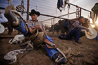 A Navajo cowboy adjusts the length of his stirrups during the annual Keith J. Boyd Memorial Rodeo in Lower Greasewood, Arizona. The Navajo have a  long tradition of rodeo and ranching. They began herding in the seventeenth century , soon after the Spanish introduced horses, cattle and sheep into the Southwest. By the 1920s, the Navajo were gathering to race horses rodeo-style, often circling the wagons to form an arena.