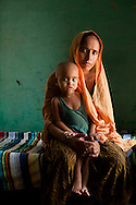 """Shashi Devi (aged 28) sits for a portrait in her house in the village of Shahpurjat, Ghaziabad, Uttar Pradesh, India. While Shashi had a tubectomy done after having 2 sons, Monika, her brother-in-law's wife, is still trying for a son after having 2 daughters. Shashi did the operation because she wanted to """"give her 2 children the best and inflation will make things difficult"""", and she believes that a """"small family is a happy family"""". She has been pushing Monika to get her husband to do an NSV so that Monika's life is not endangered since her previous pregnancies have been complicated. Photo by Suzanne Lee"""