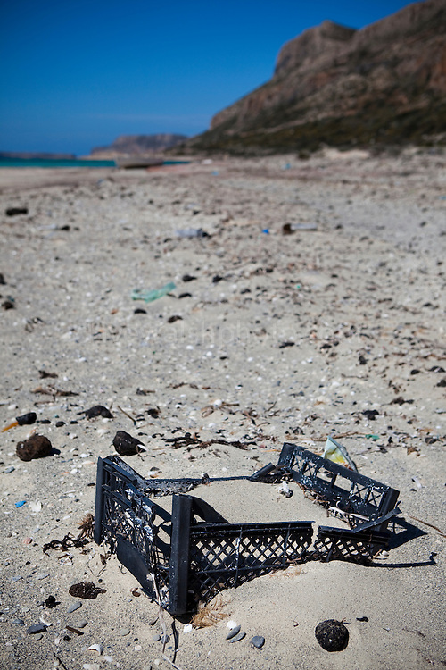 Plastic crate and tarballs from oil spills washed up on Balos Beach, on Gramvousa peninsula, in north western Crete, Greece. The beach is famous for its white sands and turquoise waters and is a protected nature reserve. The Mediterranean contains a huge amount of disgarded plastics, 15% of which ends up on beaches.