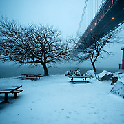 December 26, 2010 - New York, NY : Icy wind and snow whip down the Hudson River, beneath the George Washington Bridge and past the little red lighthouse on Manhattan at dusk on the day after Christmas...The Boxing Day storm pummeled the Eastern seaboard, burying New York City under over a foot of snow.