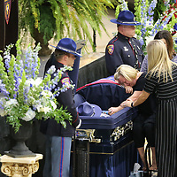 Chelsea Smith is surrounded by family and freinds as she mourns the loss of her husband, Mississippi Highway Patrol Officer Cpl. Kenneth Josh Smith,  before his service Thursday afternoon in Corinth.