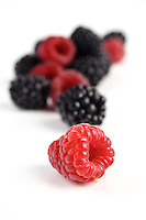 Red and black berries on white background