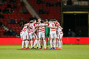 The Doncaster Rovers team assemble in a huddle before the EFL Sky Bet League 1 match between Doncaster Rovers and Barnsley at the Keepmoat Stadium, Doncaster, England on 15 March 2019.