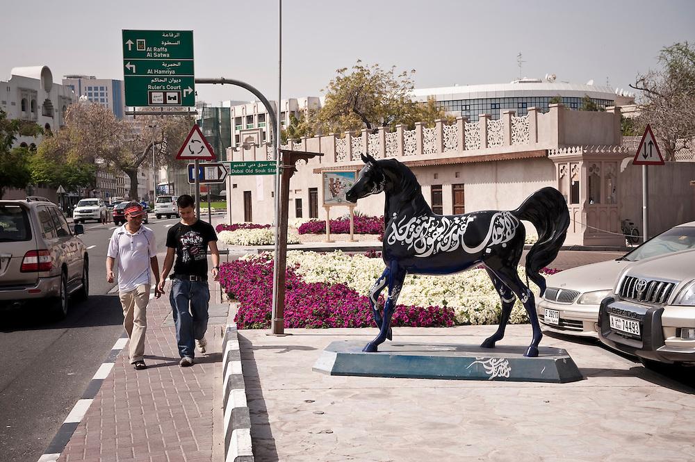 Two men walk past a sculpture of a horse near the Bastakiya area of Dubai, UAE. Archive of images of Dubai by Dubai photographer Siddharth Siva