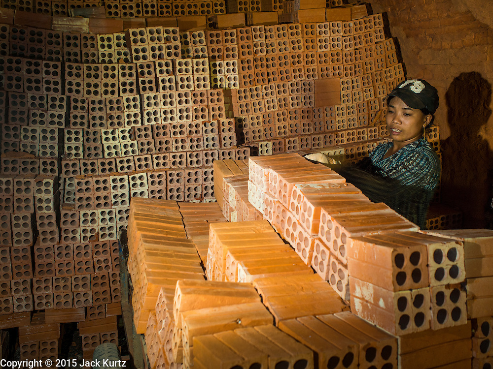 26 FEBRUARY 2015 - PHNOM PENH, CAMBODIA: Workers stack bricks on a handcart in a kiln at a brick making factory on the outskirts of Phnom Penh.    PHOTO BY JACK KURTZ
