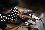A nurse examines a child at the Libreville health center in Man, Cote d'Ivoire on Wednesday July 24, 2013.