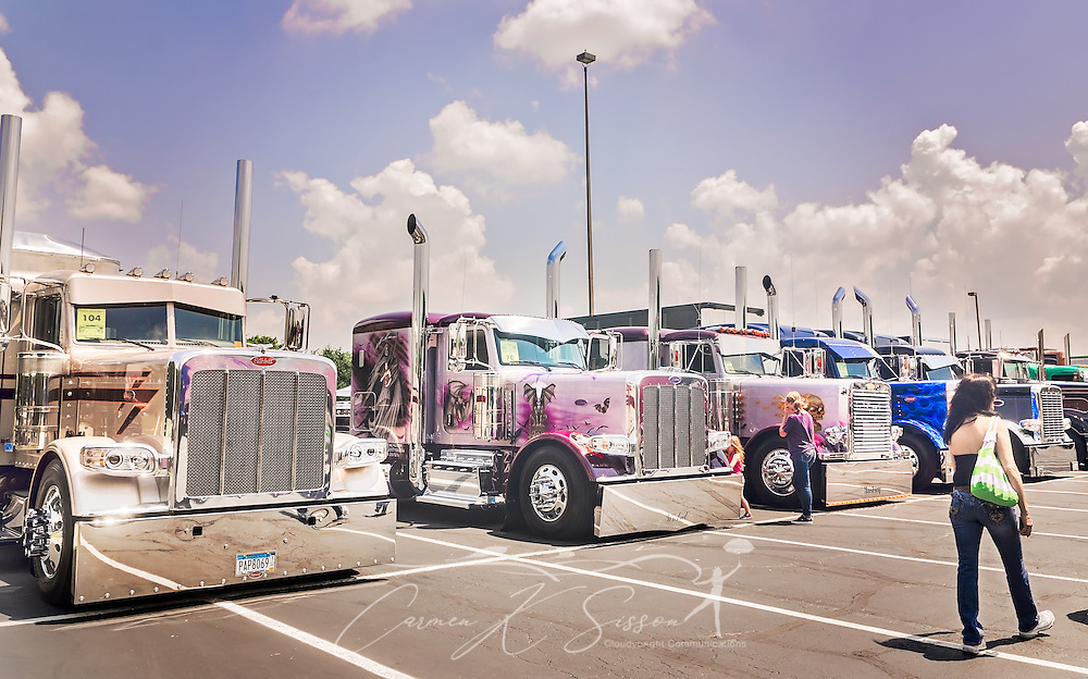 A woman walks past a row of big rigs at the 34th annual Shell Rotella SuperRigs truck beauty contest, June 11, 2016, in Joplin, Missouri. SuperRigs, organized by Shell Oil Company, is an annual beauty contest for working trucks. Approximately 89 trucks entered this year's competition. (Photo by Carmen K. Sisson/Cloudybright)