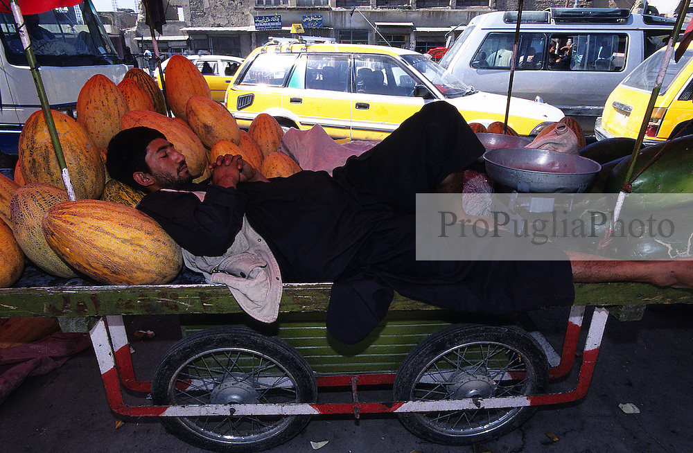 On the busy street of Kabul a melon vendor takes some time off for a sleep