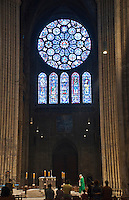 Our Lady of Chartres Cathedral, Chartres, France. View across the Chancel to the exquisite stained glass windows of the south Transept.The rose is dedicated to Christ, who is shown in the central oculus, surrounded by adoring angels. Two outer rings of twelve circles each contain the 24 Elders of the Apocalypse. The central lancet beneath the rose shows the Virgin carrying the infant Christ. Either side of this are four lancets showing the four evangelists sitting on the shoulders of four Prophets. The Counts of Dreux-Bretagne are depicted with their arms in the bases of the lancets.