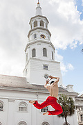 Kanji Segawa a dancer with the Alvin Ailey American Dance Theater performs during the opening ceremonies for the Spoleto Festival USA with historic St Michael's Church in the background on May 25, 2012 in Charleston, South Carolina. The 17-day performing arts festival will include more than 140 performances on stages throughout Charleston.