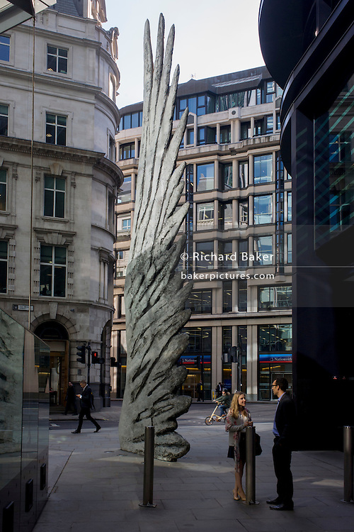 City workers talk under the giant artwork of a bronze wing during lunchtime in London's financial district. As light reflects off nearby office buildings, the lunchtime crowd walk past this giant artwork on their way to meetings and sandwich bars. The ten-metre-tall bronze sculpture is by President of the Royal Academy of Arts, Christopher Le Brun, commissioned by Hammerson in 2009. It is called 'The City Wing' and has been cast by Morris Singer Art Founders, reputedly the oldest fine art foundry in the world.