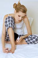 young woman sitting and applying nail polish on toe nails