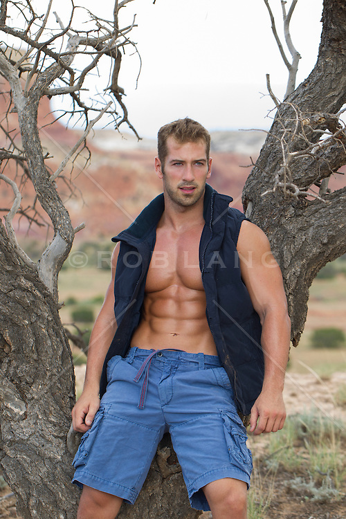 good looking twenty something year old man outdoors leaning against a dead tree in the desert