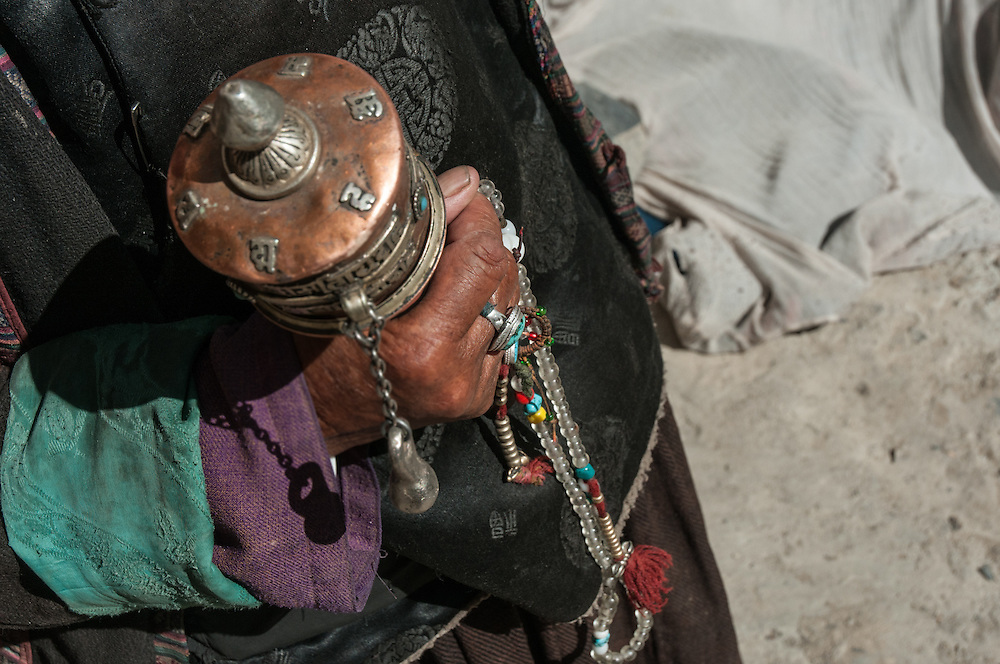 Old woman is holding her prayer wheel, Hinju, India.