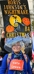 © Licensed to London News Pictures. 30/10/2019. London, UK. A Brexit protester holds a 'BORIS JOHNSON'S NIGHTMARE B4 CHRISTMAS' halloween sign outside Houses of Parliament. On Tuesday 29 October 2019 MPs voted for a UK general election on 12 December 2019. Photo credit: Dinendra Haria/LNP
