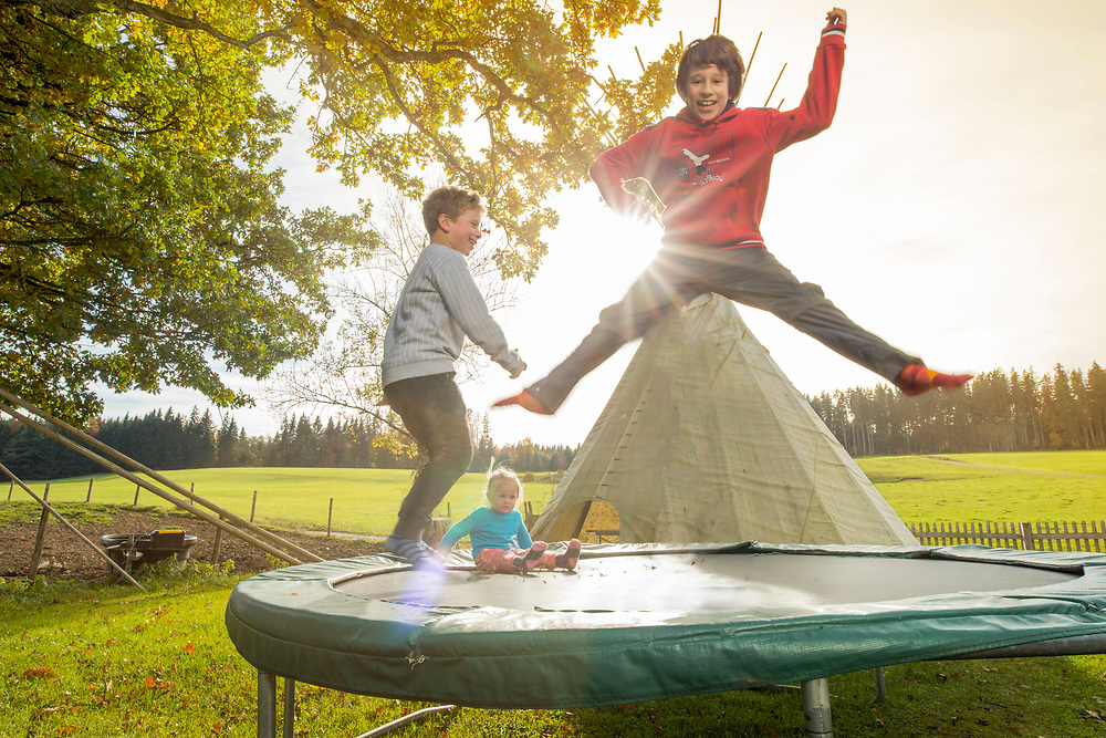 Children jumping on a trampolin having fun in the nature during an autmn day