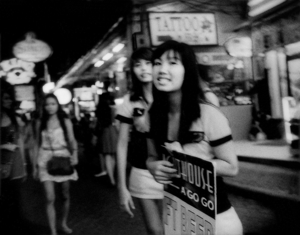 "Young female touts sent out on ""Walking Street"" to attract male customers into a go-go bar.  Walking Street, which is lined with go-go bars and clubs, becomes a pedestrian street filled with a throng of tourists; male, female and even children every night.  Pattaya, Thailand."