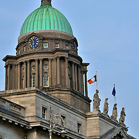 Custom House Dome Close Up in Dublin, Ireland <br /> The Custom House dome deserves a close up.  Above the pediment are statues of Neptune, Mercury, Industry and Plenty.  Between the Corinthian columns are arched and rounded windows and above them are four clocks. Standing on the top of the green copper dome is a 16 foot sculpture of Commerce.  In 1921, the dome melted during an intense fire set by the IRA that engulfed the Custom House. Ardbraccan limestone was used for the reconstruction.  This gives it a brownish hue in contrast to the rest of the white façade.