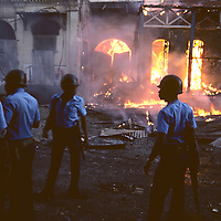 Haiti, Port-au-Prince, Soldiers stand by burning house during political violence leading up to 1988 Presidential elections
