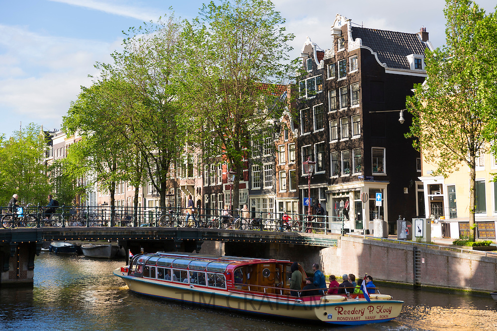Tourists canal sightseeing boat cruise trip pass restaurants, bars and houses on canalside street, Herengracht, Amsterdam, Holland