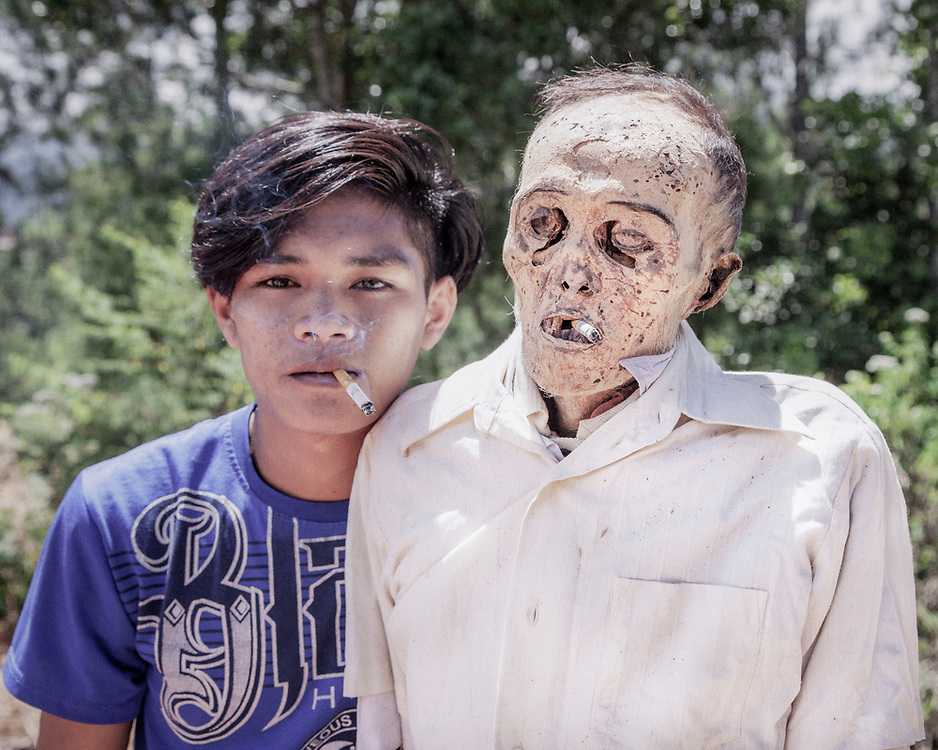 A family member sharing a cigarette with his dead relative poses for a portrait.<br />